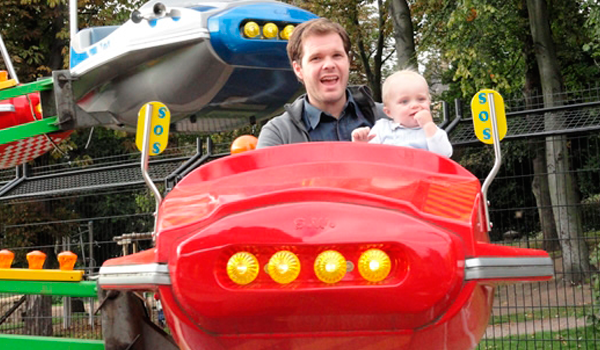 Man and child on a space ride attraction.