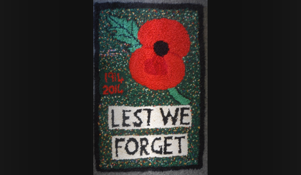 Memorial tapestry with poppy and. the words lest we forget
